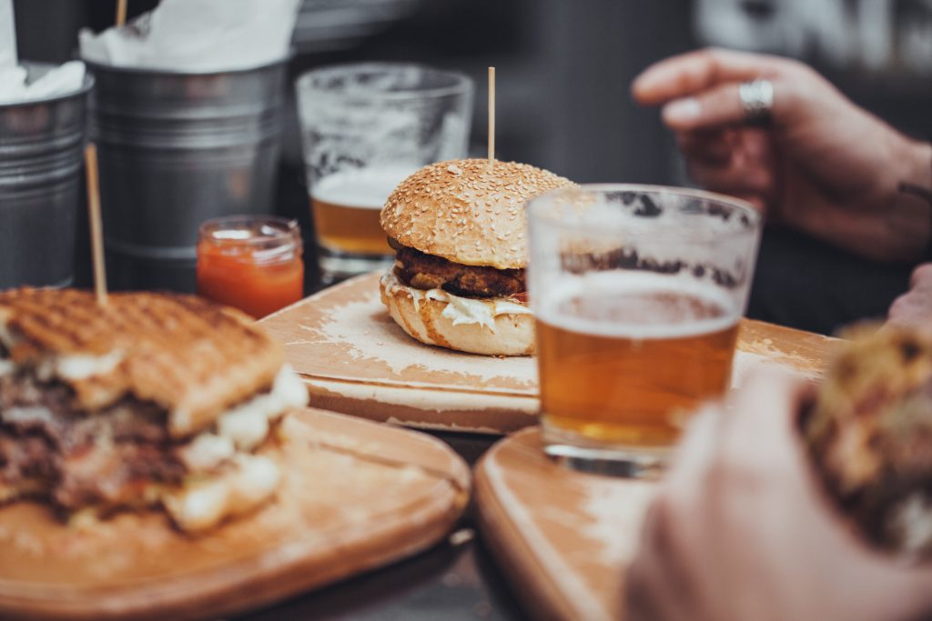Delicious Pub Food. Burgers And Glasses Of Beer On Wooden Plates
